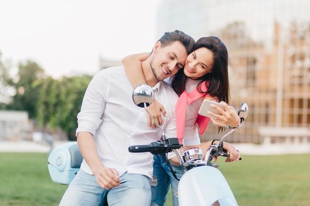 Elegancka kobieta delikatnie dotyka przystojnego mężczyzny na skuterze i robi z nim selfie