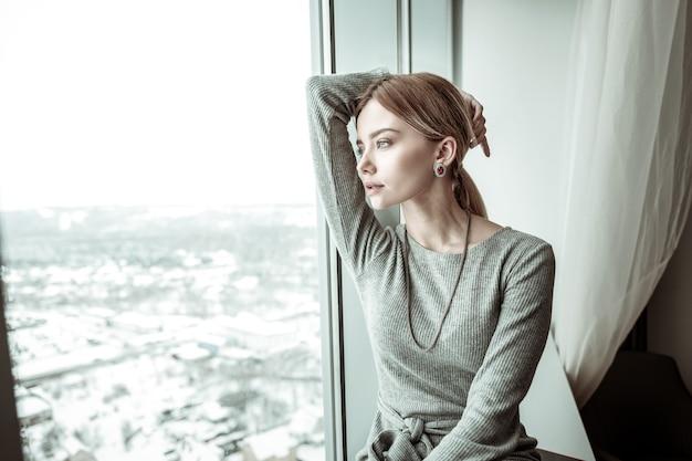 Elegancka kobieta. elegancka modna blondynka patrząc w okno podziwiając widok