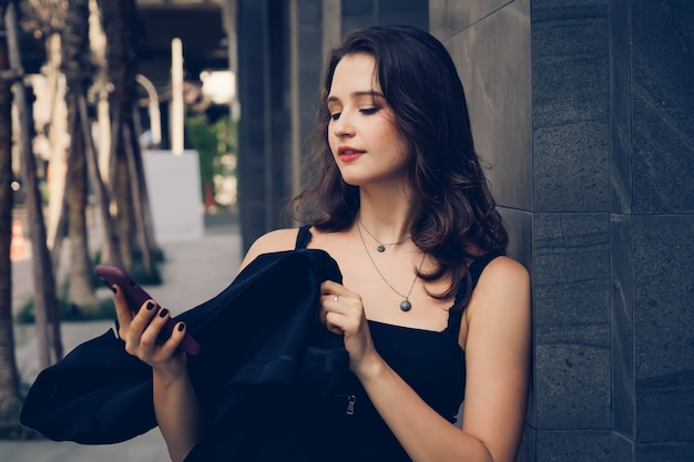 Elegancka kobieta na zewnątrz biura i przy użyciu telefonu komórkowego.
