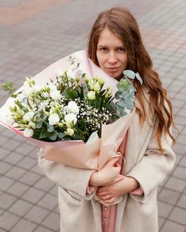 Elegancka kobieta na zewnątrz trzymając bukiet kwiatów