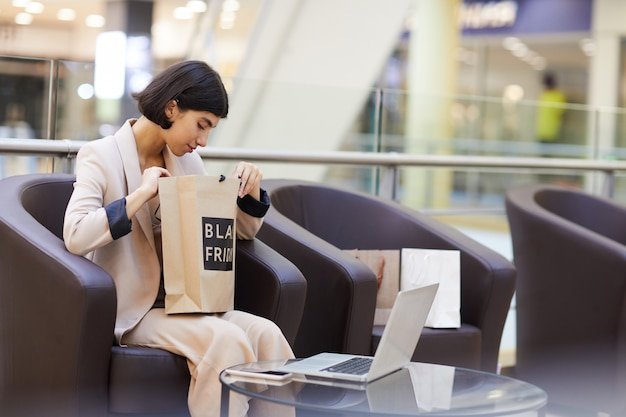 Elegancka kobieta, patrząc na torbę na zakupy