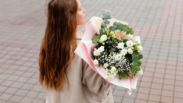 Elegancka kobieta poza trzymając bukiet kwiatów