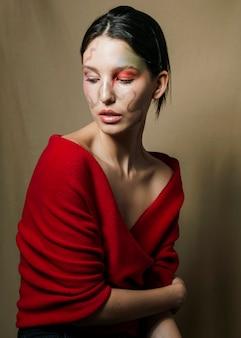 Elegancka kobieta pozuje w czerwonej bluzce
