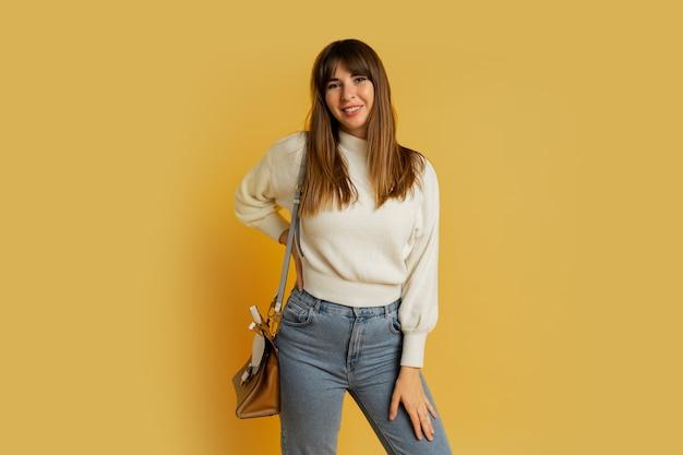 Elegancka kobieta pozuje w studio na żółto. ubrany w biały wełniany sweter i dżinsy.
