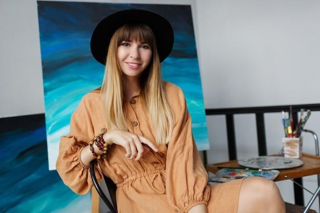 Elegancka kobieta pozuje z nowymi jej dziełami sztuki.