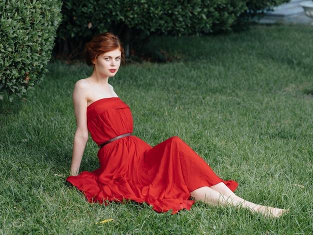 Elegancka kobieta siedząca na trawie w czerwonej sukience z dekoracją