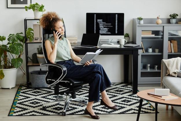 Elegancka kobieta siedzi na krześle z notatnikiem i rozmawia przez telefon komórkowy podczas pracy w biurze