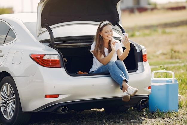 Elegancka kobieta siedzi w bagażniku z telefonem komórkowym