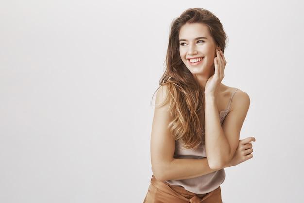 Elegancka kobieta śmiejąca się i zalotna, patrząc w lewo