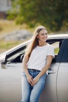 Elegancka kobieta stojąca przy samochodzie