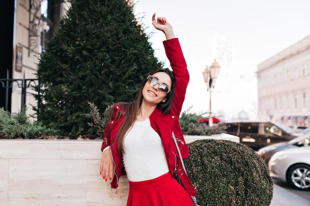 Elegancka kobieta stojąca w pobliżu zielonego drzewa i wyrażająca szczęście