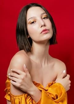Elegancka kobieta stwarzających w żółtej sukni i odkrytymi ramionami