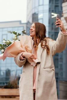 Elegancka kobieta trzyma bukiet kwiatów na zewnątrz i biorąc selfie