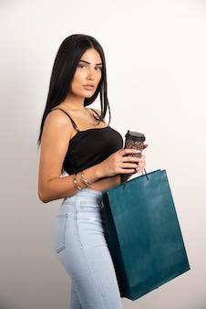 Elegancka kobieta trzyma kawę i torby na zakupy. wysokiej jakości zdjęcie