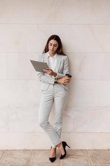 Elegancka kobieta trzymając tabletkę i filiżankę kawy