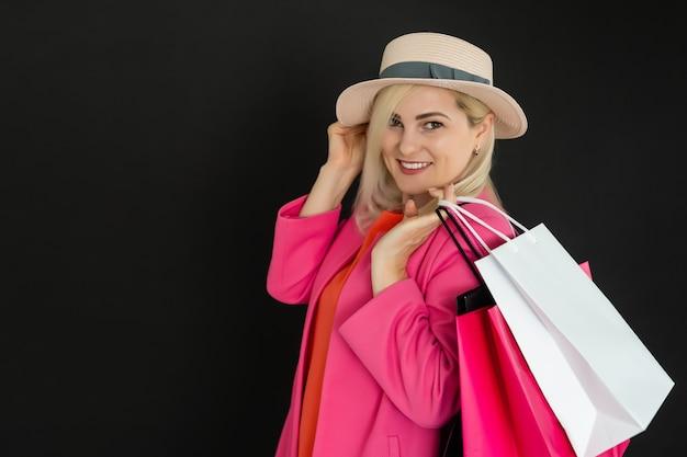 Elegancka kobieta trzymająca czarne torby na zakupy, koncepcja czarnego piątku