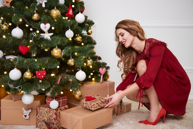 Elegancka kobieta umieszcza prezenty pod choinką