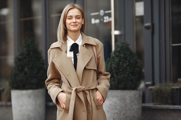 Elegancka kobieta w brązowym płaszczu w wiosennym mieście