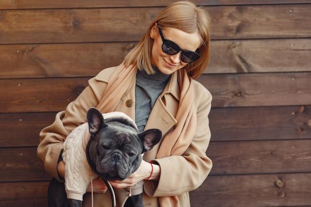 Elegancka kobieta w brązowym płaszczu z czarnym buldogiem