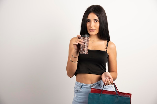 Elegancka kobieta w czarnej top gospodarstwa torby i kawy. wysokiej jakości zdjęcie
