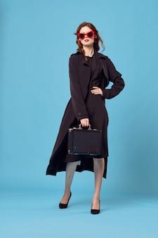 Elegancka kobieta w czarnym płaszczu bizneswoman pracuje potem na wakacjach