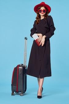 Elegancka kobieta w czarnym płaszczu pasażera podróży styl życia niebieskie tło. zdjęcie wysokiej jakości