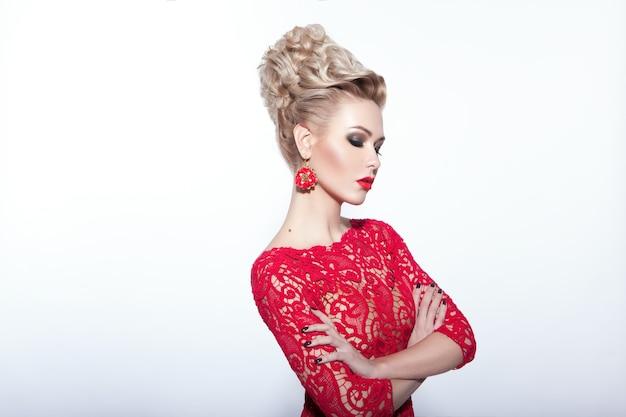 Elegancka kobieta w czerwonej sukience i akcesoriach, na białym tle, pozuje z założonymi rękami