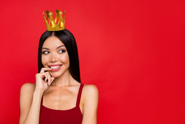Elegancka kobieta w czerwonej sukience pozuje na czerwonej ścianie