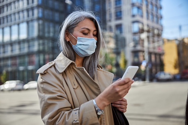 Elegancka kobieta w masce medycznej korzystająca z telefonu komórkowego na ulicy