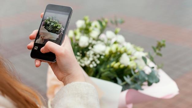 Elegancka kobieta w mieście robi zdjęcie bukiet kwiatów