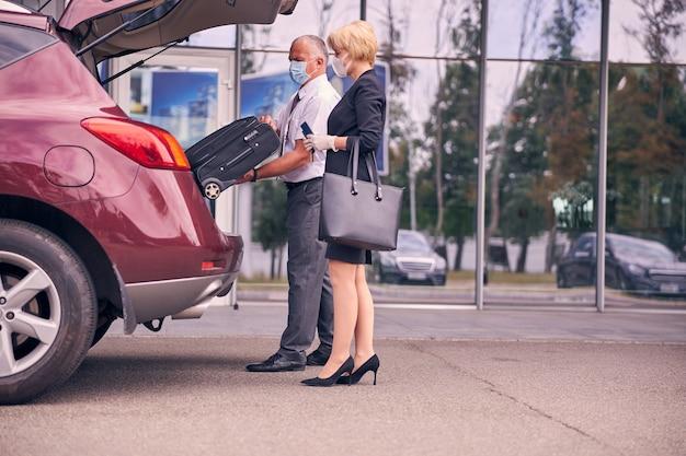 Elegancka kobieta w ochronnej masce na twarz trzymająca bilet i paszport, podczas gdy dżentelmen wyciąga walizkę podróżną z bagażnika samochodu