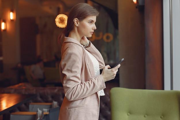 Elegancka kobieta w różowej kurtce spędza czas w kawiarni