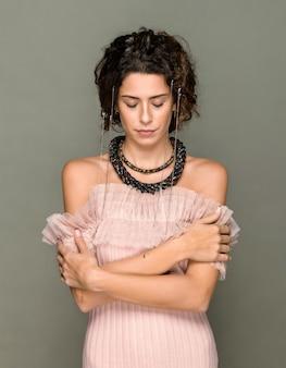 Elegancka kobieta w różowym topie z odkrytymi ramionami z kryształowymi akcesoriami w podwójnym naszyjniku pozuje skromnie ze spuszczonymi oczami na szarym tle studia