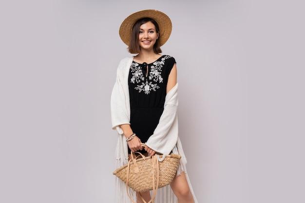 Elegancka kobieta w słomkowym kapeluszu na białym tle.