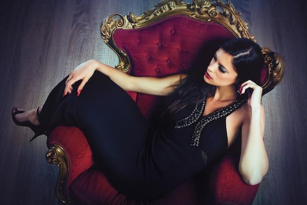 Elegancka kobieta w stroju wieczorowym siedzi na barokowym fotelu
