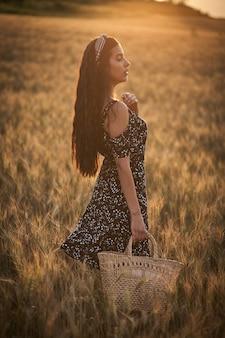 Elegancka kobieta w sukience z koszem w polu pszenicy o zachodzie słońca.