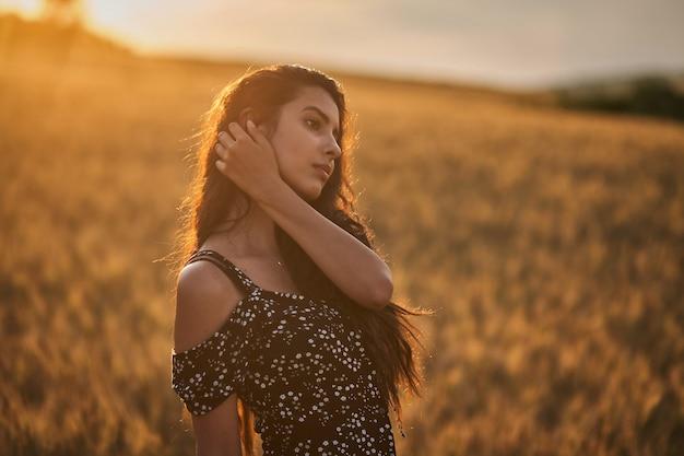 Elegancka kobieta w sukni w polu pszenicy o zachodzie słońca.