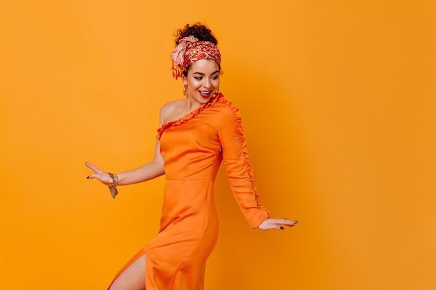 Elegancka kobieta w sukni z odkrytym ramieniem zalotnie pozuje na pomarańczowej przestrzeni.
