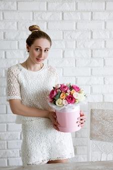 Elegancka kobieta z prezentem. bukiet luksusowych kwiatów. kolorowe róże bokserskie w różowym pudełku w kształcie walca. piękny i zmysłowy prezent na 8 marca, walentynki