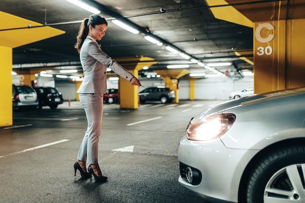 Elegancka kobieta zamyka samochód na klucze w podziemnym parkingu.