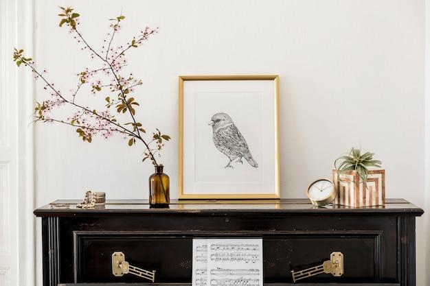Elegancka kompozycja we wnętrzu salonu z czarnym pianinem, złotą ramą plakatową makiety, wiosennymi kwiatami, dekoracją, zegarem i stylowymi dodatkami w nowoczesnym wystroju domu.