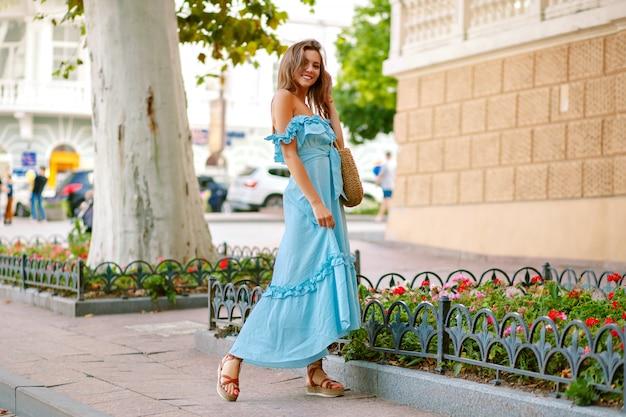 Elegancka ładna kobieta ubrana w modną niebieską sukienkę maxi, pozuje w parku miejskim