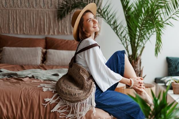 Elegancka ładna kobieta w słomkowym kapeluszu i białej bluzce, pozowanie w domu, siedząc na łóżku