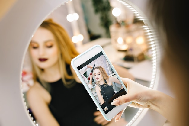 Elegancka ładna młoda kobieta robienie zdjęć na telefon w lustrze podczas robienia fryzury w salonie fryzjerskim. stylowy modny model, przygotowujący do imprezy, uroczystości, luksusowy wygląd