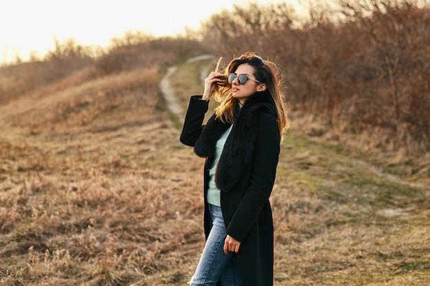 Elegancka ładna modelka w stylowych okularach przeciwsłonecznych i płaszczu, piękna młoda kobieta. strzał na zewnątrz.
