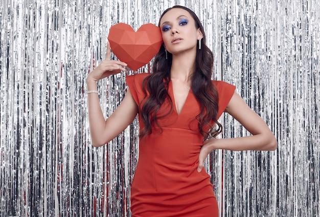 Elegancka latynoska brunetki kobieta w luksusowej czerwonej sukni trzyma papierowego serce