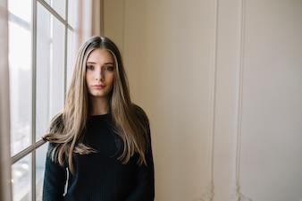Elegancka młoda kobieta w czarnej odzieży w pokoju