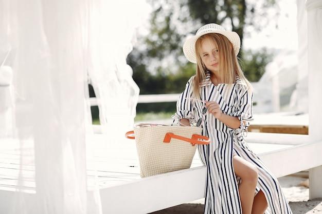 Elegancka mała dziewczynka na letnim wybrzeżu