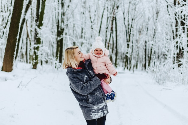 Elegancka mama z dzieckiem chodzić na ulicy w zimie