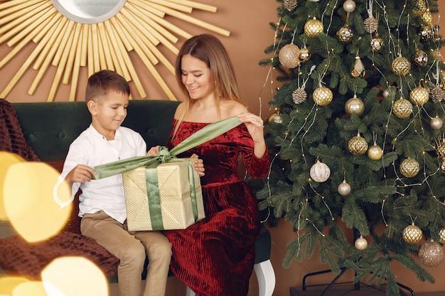 Elegancka matka siedzi w domu z małym synkiem